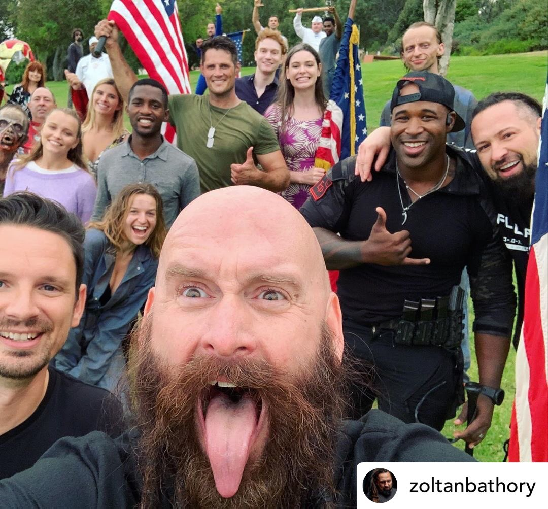Five Finger Death Punch members pictured with the cast of the music video for Living The Dream